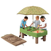 "2 years & up. This sand and water table is loaded with action, including two bridges, ramps, cups, and boats. The included umbrella keeps the play table safely shaded from the sun, and the cover fastens on securely at night for protection against the elements. The lid also doubles as an exciting track for cars! Assembly required. 21""H x 26""W x 46""D."
