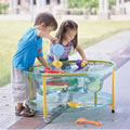 "18 months & up. Our clear sand and water table has an adjustable stand (22"" to 31 1/2"") and wheels are attached to the front for easy transport. Included is a cover to keep the box contents clean. The multi-layer design lets children experience the variation of depths and the screw on water valve allows for easy cleanup. Minor assembly. 34 3/4""L x 25 1/2""W."
