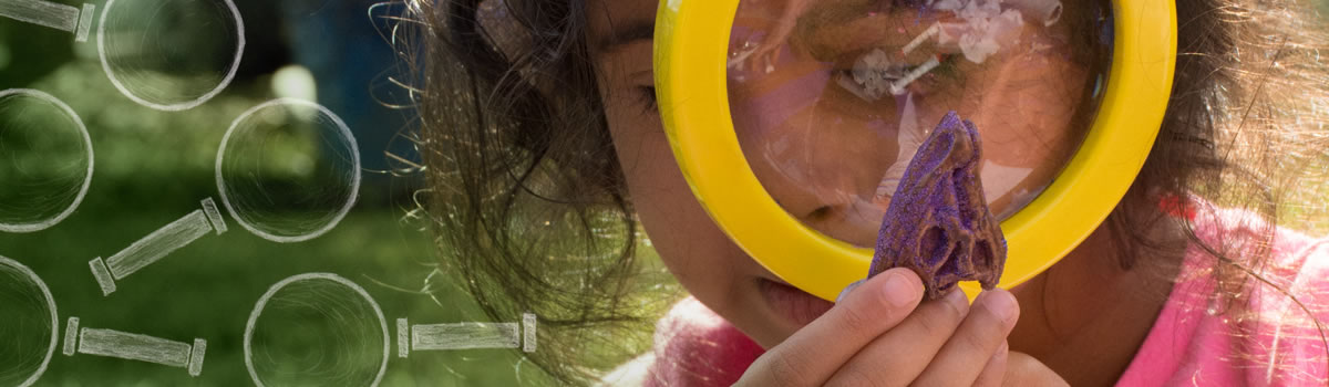 Young child using magnifier to study STEM